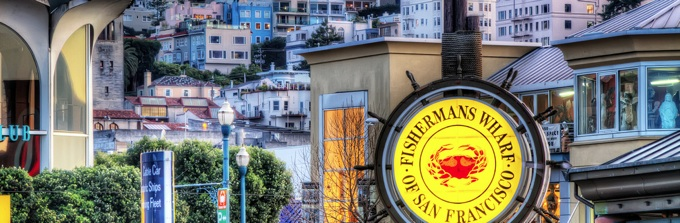 Fisherman's Wharf sign with buildings in backdrop