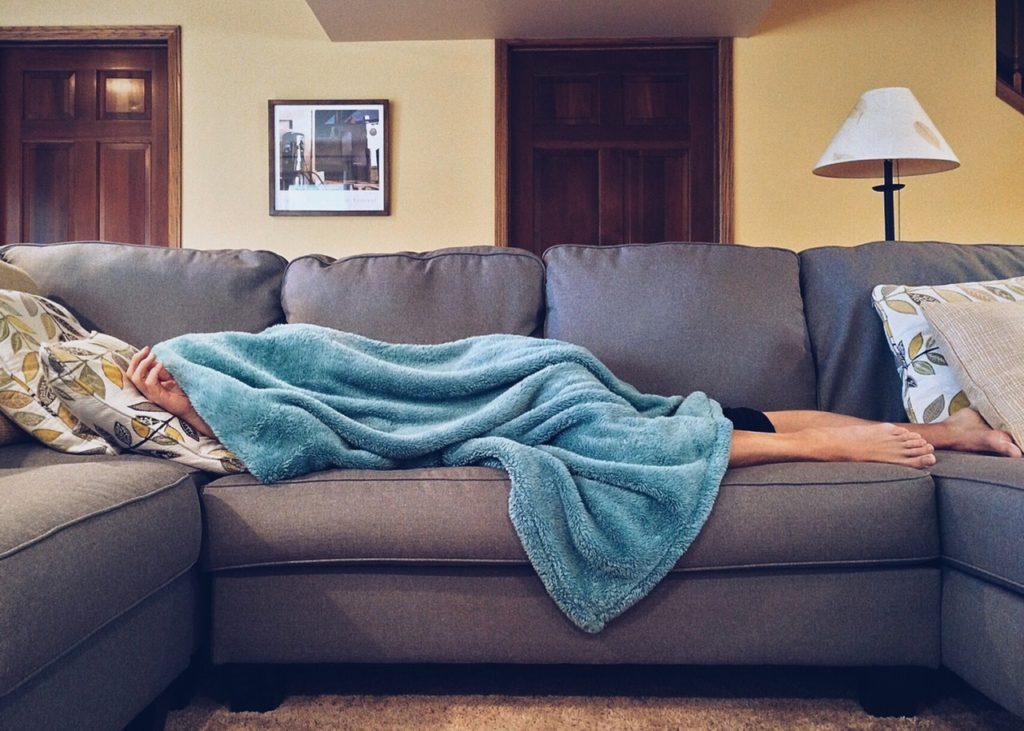 person hiding under blanket
